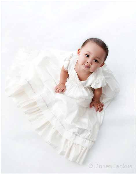 baby looking up to the photographer photographed on white wearing a christening gown in a Los Angeles portrait studio