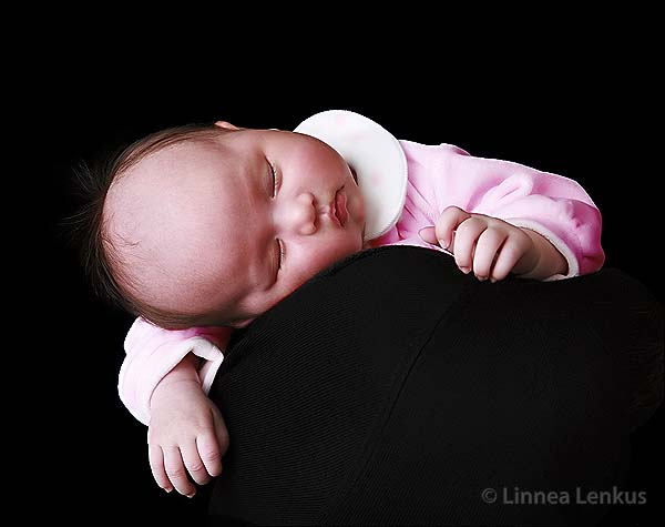 baby photography of a female baby sleeping on her mother's shoulder wearing pink