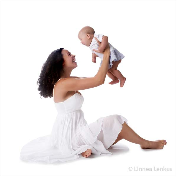 mother holding baby in the air smiling photographed by orange county baby photographer