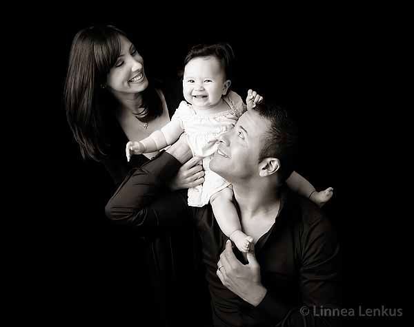 family portrait of smiling baby and parents adoring her in a California portrait studio