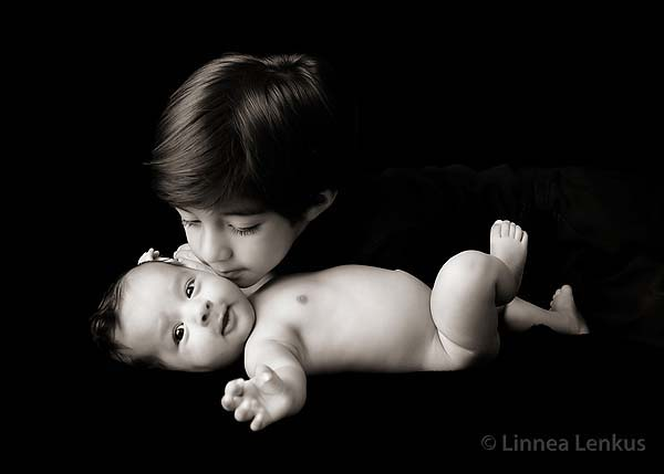 tender baby and family photography of a brother leaning over his baby brother about to give a kiss
