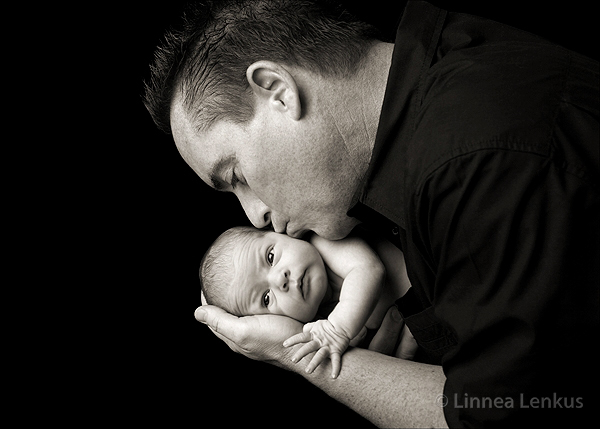 father kissing newborn baby in a photography studio portrait