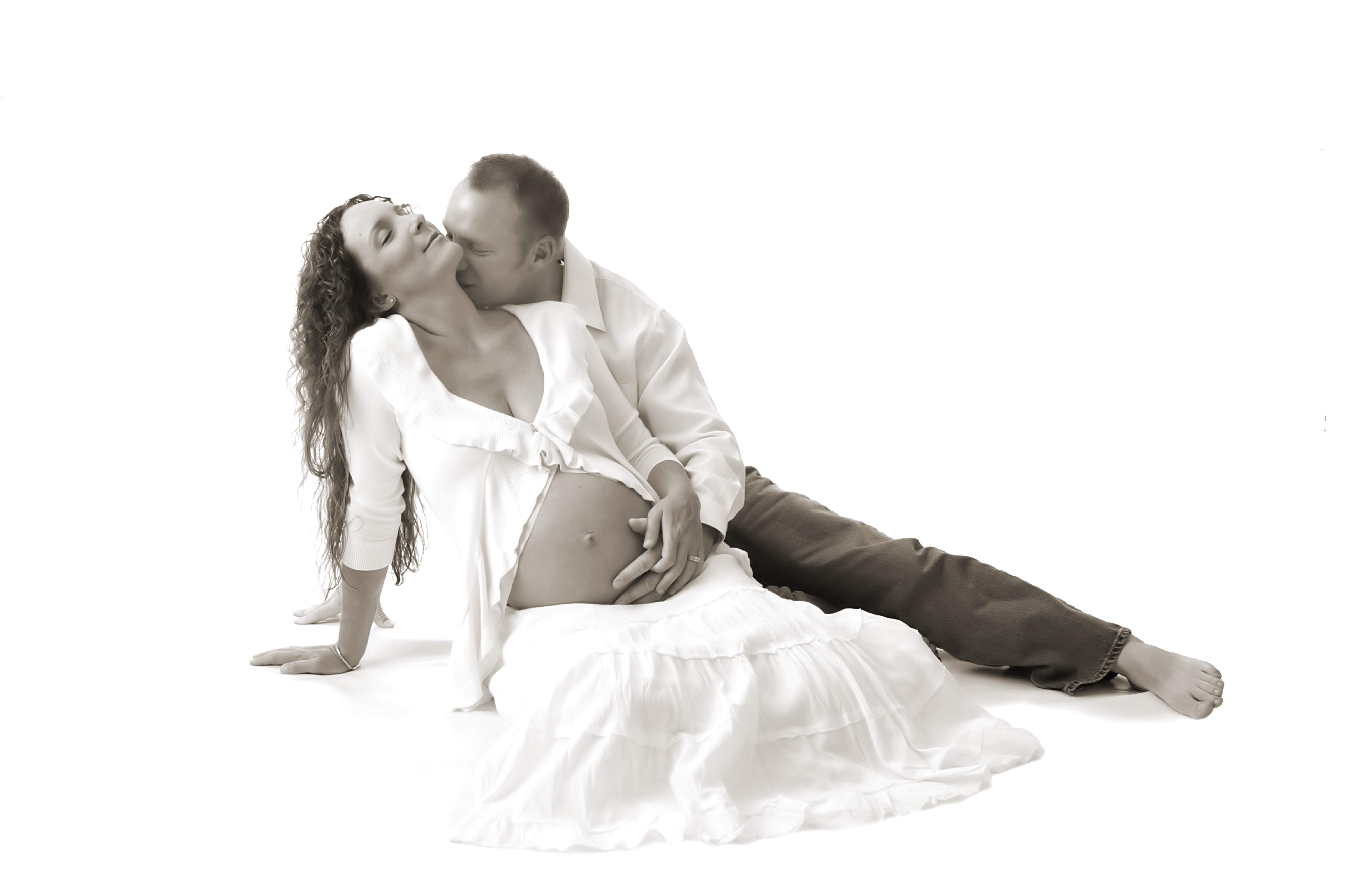 pregnant woman being kissed by her man holding her pregnant belly